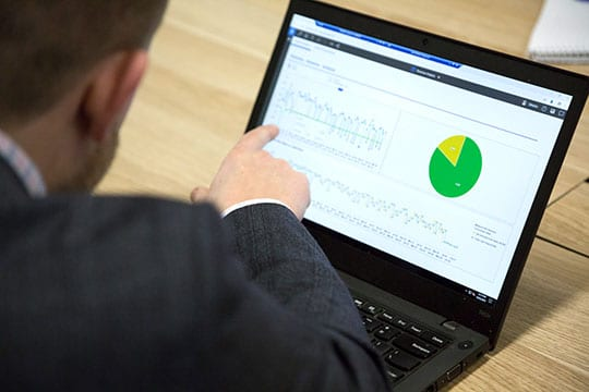 Man pointing at screen showing data charts