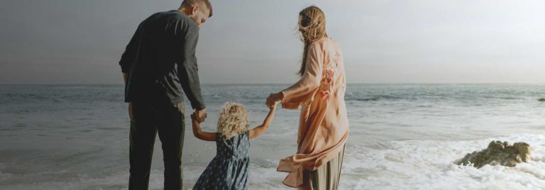 Monash IVF technology solution: Mother and father holding a child's hands at the beach