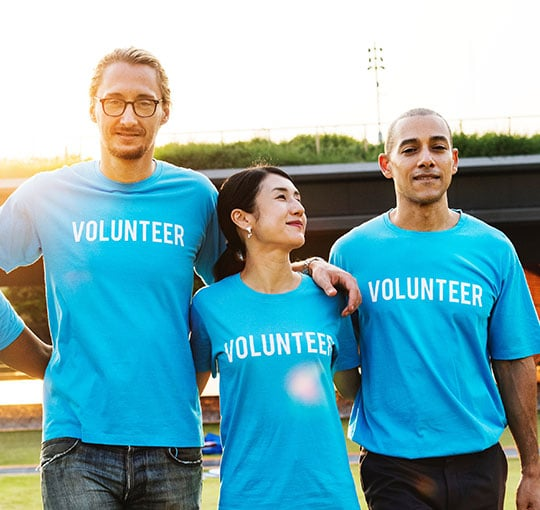 Not-for-profit industry: Four volunteers in blue shirts